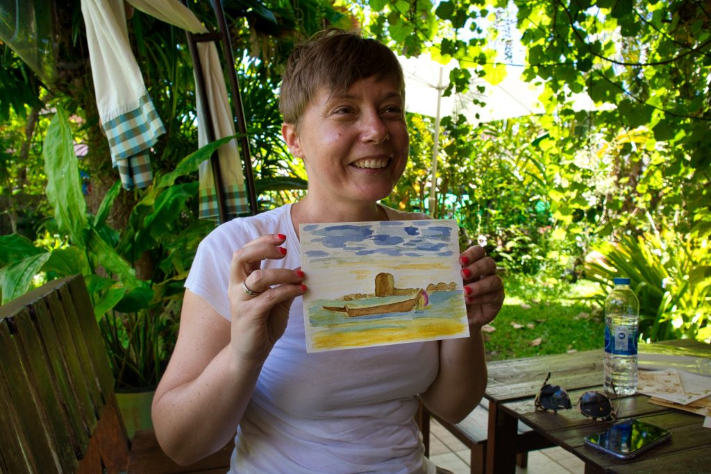a smiling woman holding a postcard painted with natural colours in koh klang, thailand.