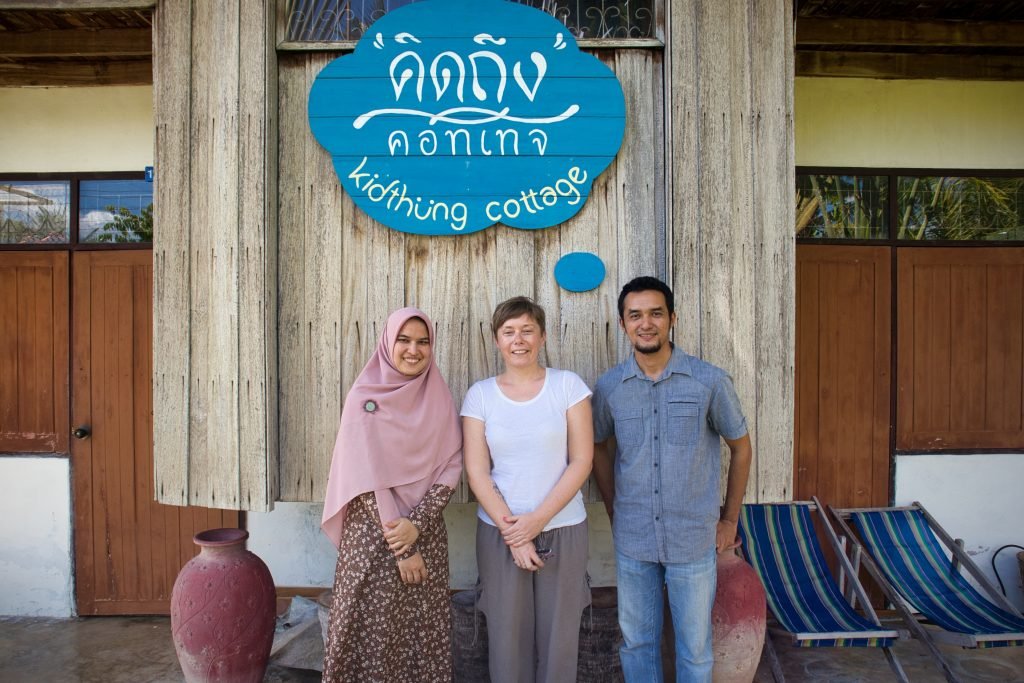 a muslim woman and a muslim man standing in front of a guest house with a foreign woman. they smile at the camera.