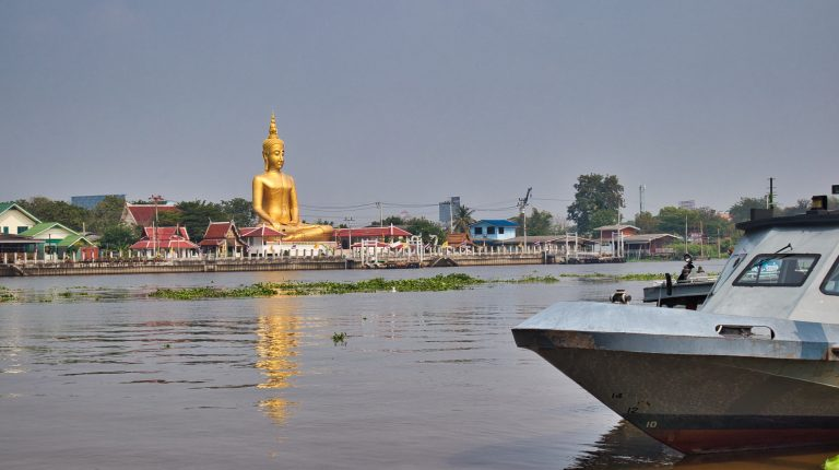 a golden buddha statue over a river in bangkok, koh kret, thailand
