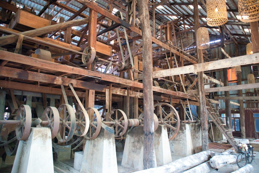 old mill parts with big wheels and wooden beams.