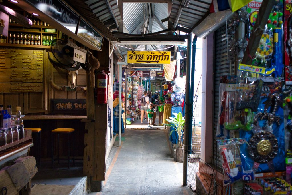 an aisle at the koh kret market with a yellow sign in Thai. In the distance you can see a tourist.