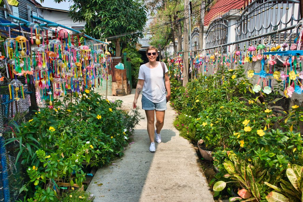 a woman walking on a colourful street on koh kret in bangkok.