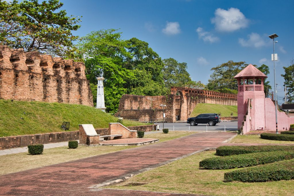 a city wall in nakhon si thammarat with a pink tower