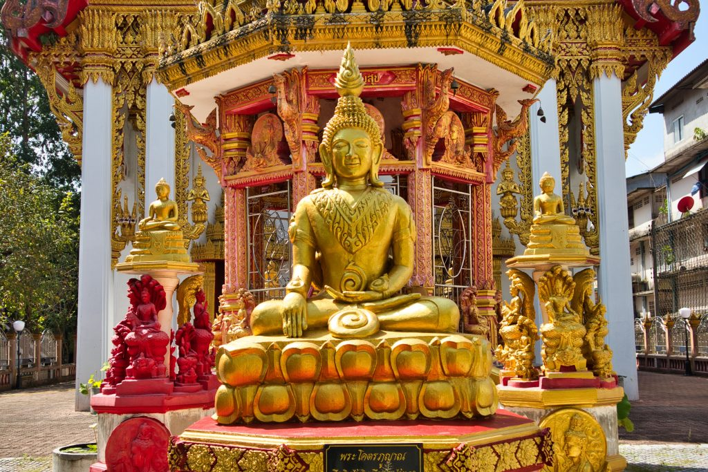 a golden buddha sits at a entrance to the temple in nakhon si thammarat in thailand