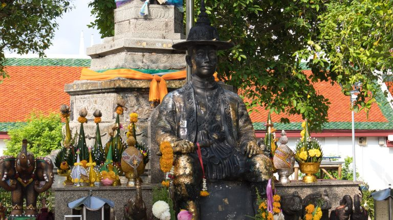 a sculpture of a king of thailand surrounded by colourful flowers in nakhon si thammarat
