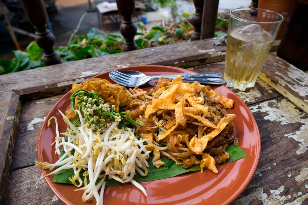 pad thai on a brown plate on a wooden table with soy beans and some egg. Koh Kret, Bangkok.
