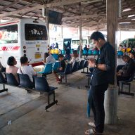 a man standing at a station in nakhon si thammarat listening to music while other passengers are waiting