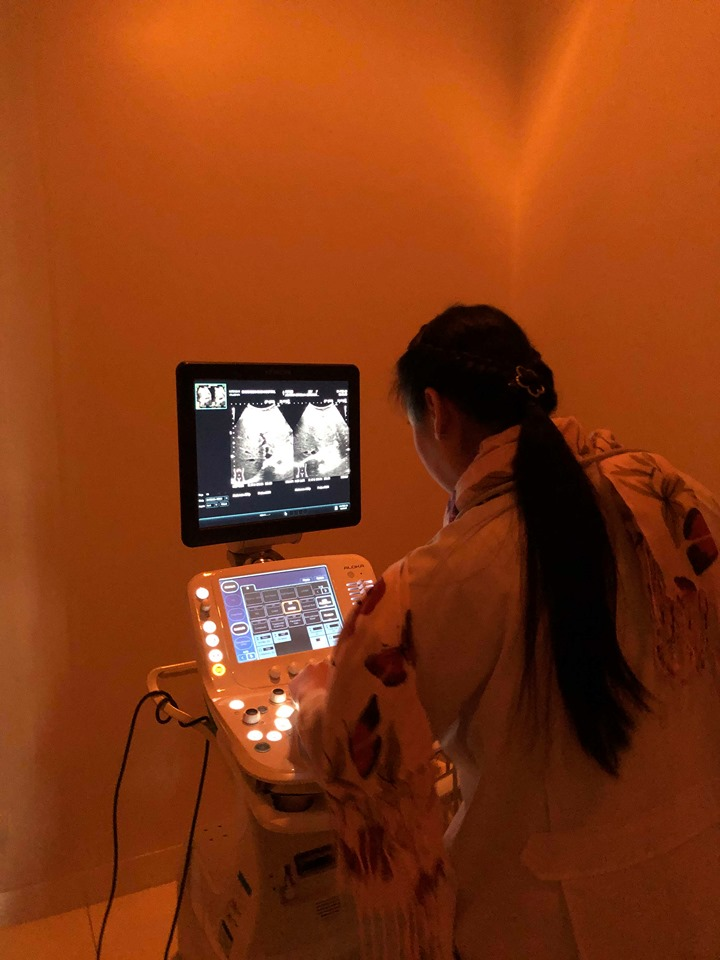 a thai doctor looks at the ultrasound monitor at the ram hospital in chiang mai.
