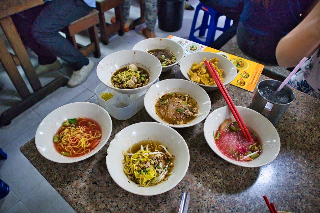 lokalne jedzenie w Bangkoku - małe talerze boat noodles w różnych kolorach na stole.