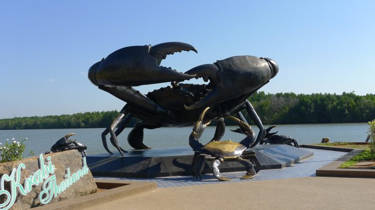 a huge crab sculpture standing on a shore of a river in krabi town, thailand.