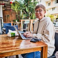 a digital nomad in chiang mai woman sitting at a wooden table in nimman social
