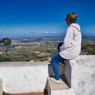a woman sits on a wall overlooking the valley in Portugal. Medical health insurance for digital nomads.