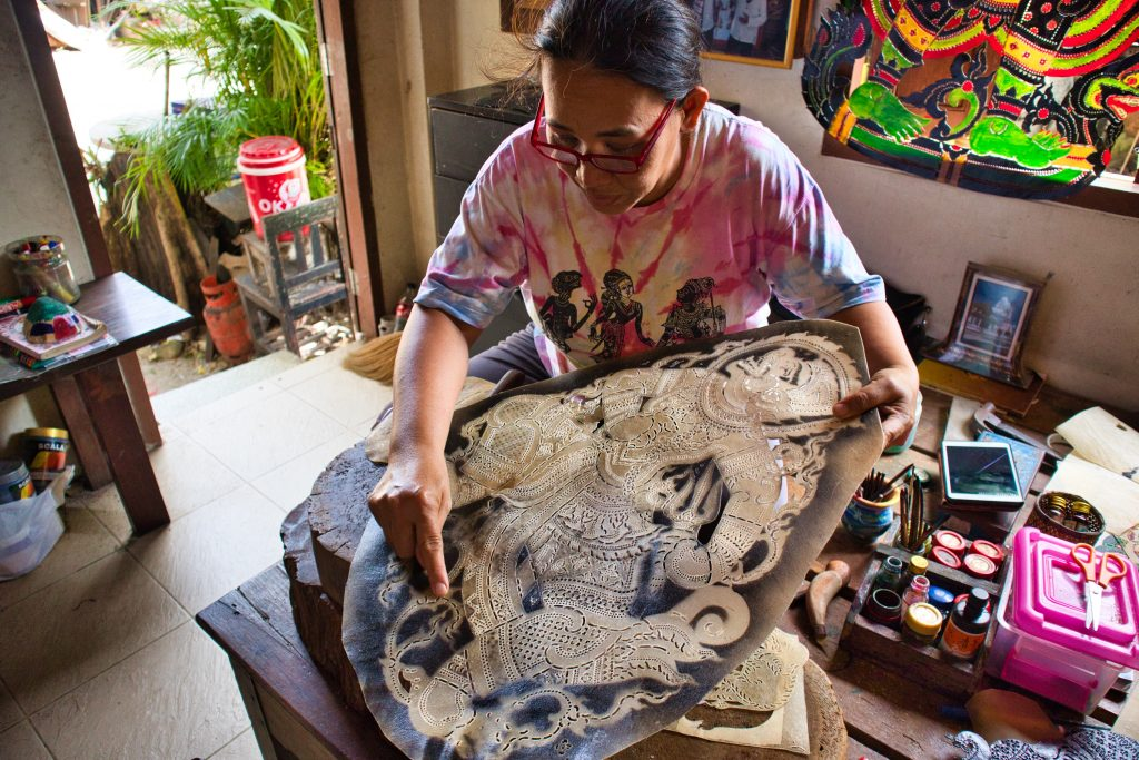 a woman shows how to make shadow puppets in nakhon si thammarat