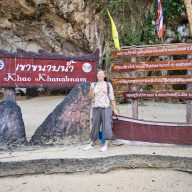 a woman standing outside of the kanabnam cave with signs in thai language.