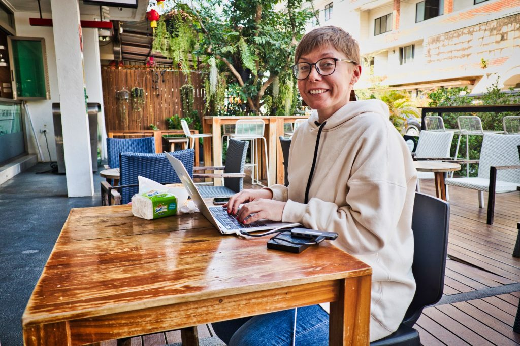 A woman in a white hoodie is sitting at a wooden table with her laptop at smiles at the camera.