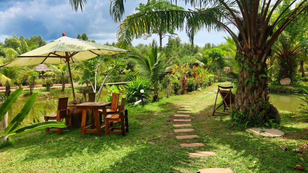 a beautiful garden with some lounge tables and chairs on koh lanta, koh lanta park life, thailand.