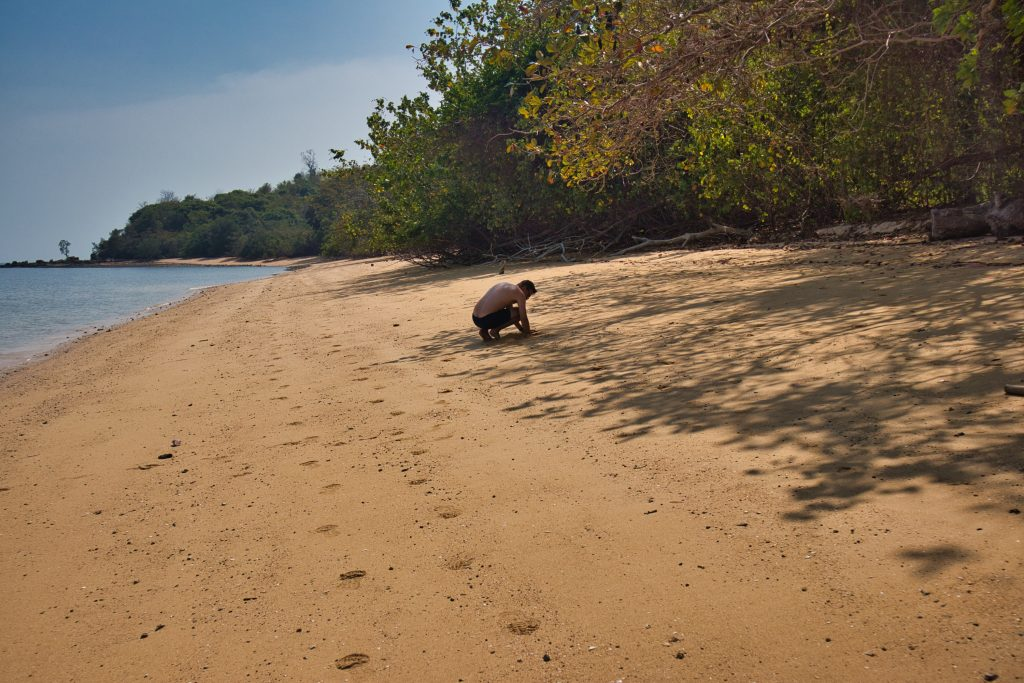 A man squatting on a beach in Thailand, building sand castles on an empty beach.