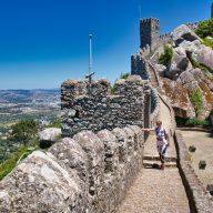 kobieta stoi na murze zamku maurow w sintrze.