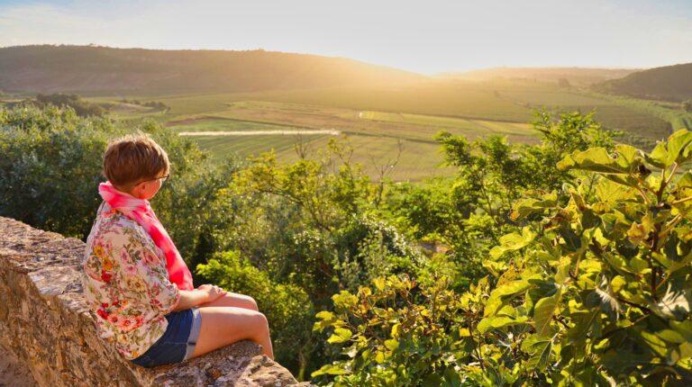 dziewczyna siedzi na murku w portugalii i patrzy sie na zachodzace slonce
