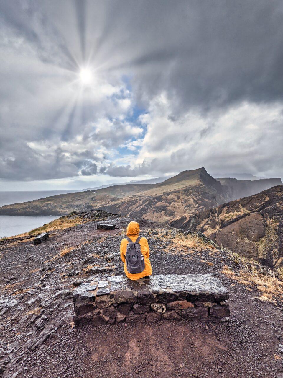 Dziewczyna w żółtej kurtce siedzi na ławce na Półwyspie Świętego Wawrzyńca.
