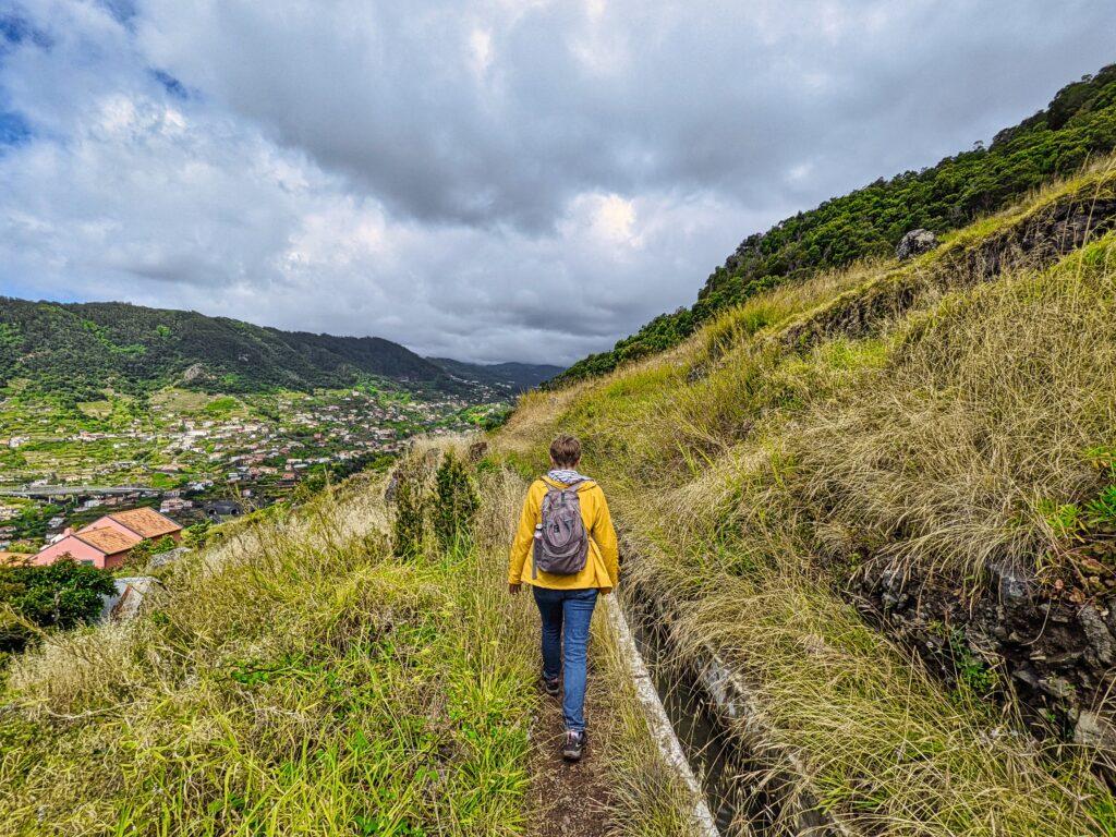 Dziewczyna w żółtej kurtce idzie lewadą na Maderze.