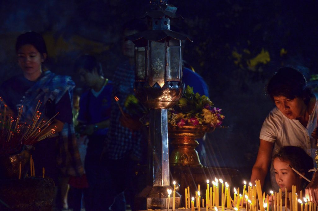 Father and child lighting a candle during Makha Bucha in Chiang Mai