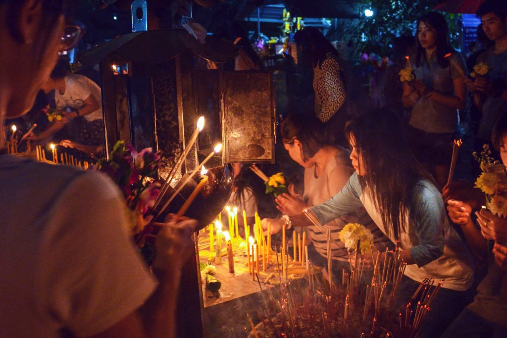 Woman lighting a candle during Makha Bucha in Chiang Mai